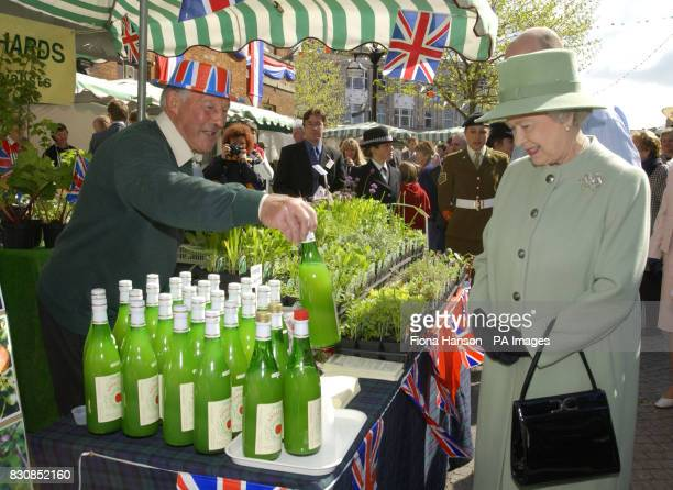 Britain's Queen Elizabeth II looks at some local apple juice at a farmer's market in Taunton Somerset on the second day of a fifteen day tour to...
