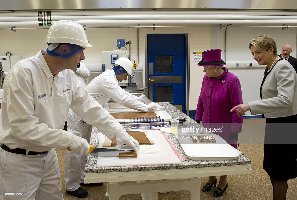 Britain's Queen Elizabeth II (2R) looks on as Rob Robinson (L) cuts Mars bars in the pilot plant, part of the research and development, during a visit to Mars Chocolate UK in Slough, southern England on April 5, 2013. The Queen and the Duke of Edinburgh visited the Mars factory in Slough that has been producing chocolate for over 80 years. A plaque was unveiled to commemorate the visit in which the Queen toured the facility and spoke with members of staff.