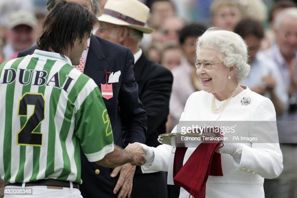 Britain's Queen Elizabeth II make a presentation to Piki DiazAlberdi of Dubai after they beat the Broncos 12 to 10 in the Queen's Cup Final at the...