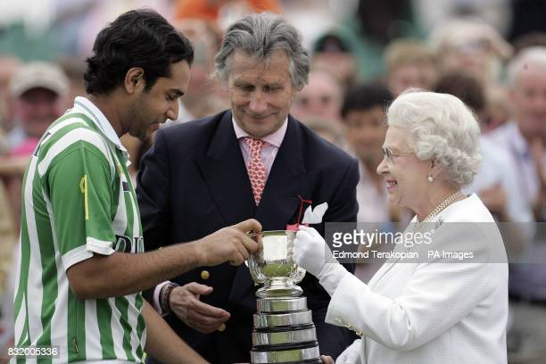 Britain's Queen Elizabeth II make a presentation to the captain Dubai Tariq Albwardy after they beat the Broncos 12 to 10 in the Queen's Cup Final at...