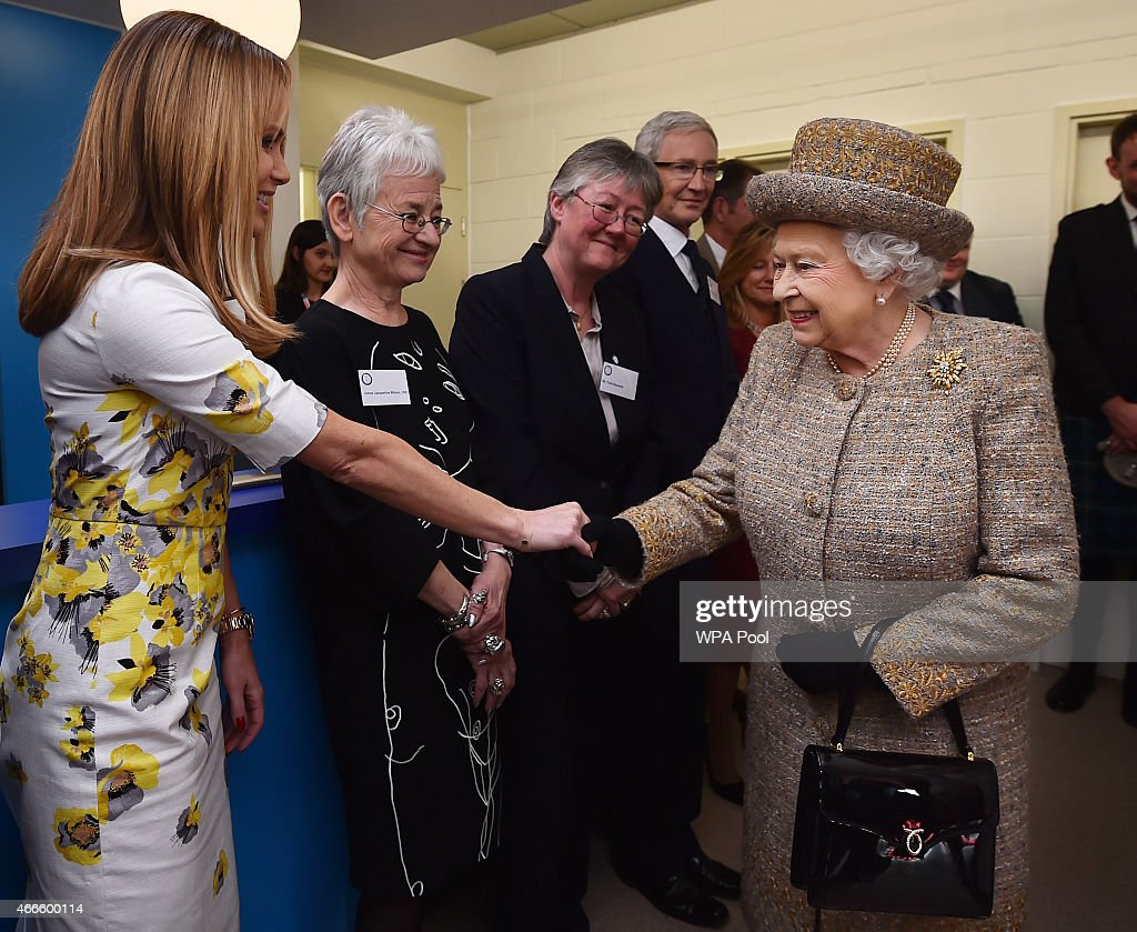 Britain's Queen Elizabeth II meets British actress and patron Amanda Holden as she attends the opening of the new Mary Tealby dog kennels at Battersea Dogs and Cats Home in London on March 17, 2015.