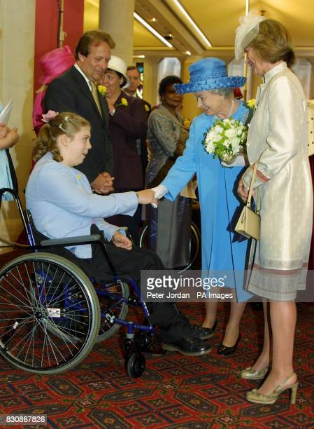 Britain's Queen Elizabeth II meets Zara Todd whilst visiting the Guild hall in London for a banquet to celebrate her Golden Jubilee as a continuing...