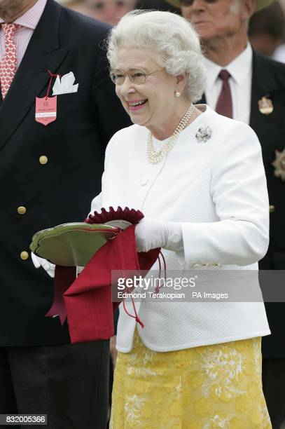 Britain's Queen Elizabeth II prepares to make a presentation the Dubai team after they beat the Broncos 12 to 10 in the Queen's Cup Final at the...