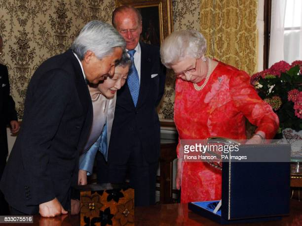 Britain's Queen Elizabeth II presents a gift of a silver rimmmed crystal bowl to the Emperor and Empress of Japan who in return present The Queen and...