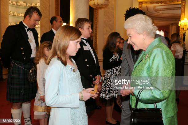 Britain's Queen Elizabeth II presents a gold Blue Peter badge to Elena Byrne from Northern Ireland who has raised funds and writes poetry for...
