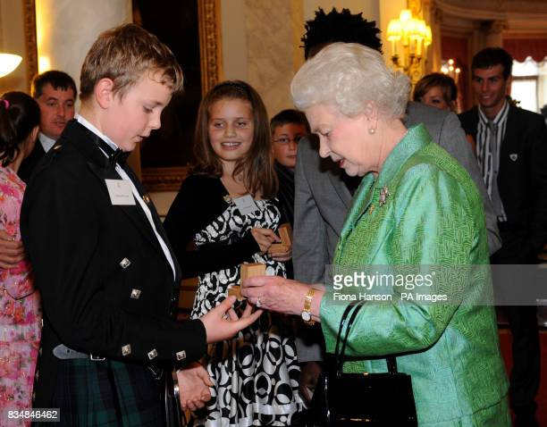 Britain's Queen Elizabeth II presents a gold Blue Peter badge to Connor Newlands from Scotland who saved his sister Gemma from drowning during a...