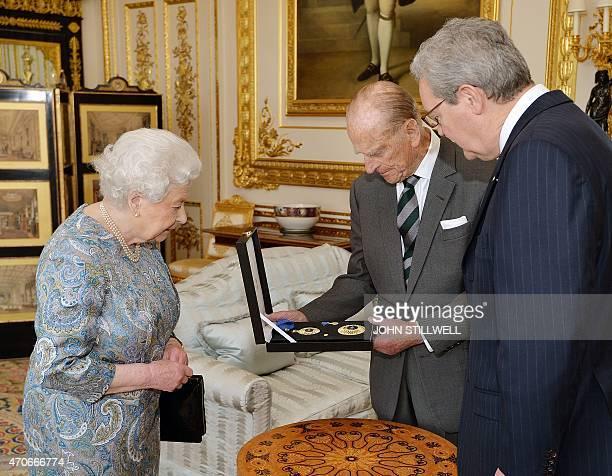 Britain's Queen Elizabeth II presents Britain's Prince Philip Duke of Edinburgh with the Insignia of a Knight of the Order of Australia as Australian...