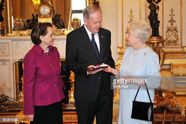 Britain's Queen Elizabeth II presents the Order of Merit to Former Canadian Prime Minister Jean Chretien who is accompanied by wife Aline at...