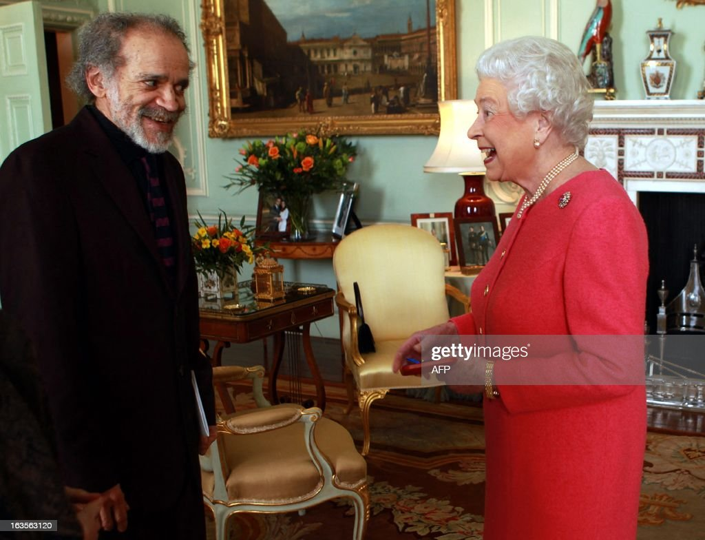 Britain's Queen Elizabeth II presents the Queen's Gold Medal for Poetry to John Agard (L) at Buckingham Palace in London on March 12, 2013. AFP PHOTO/POOL/ Sean Dempsey