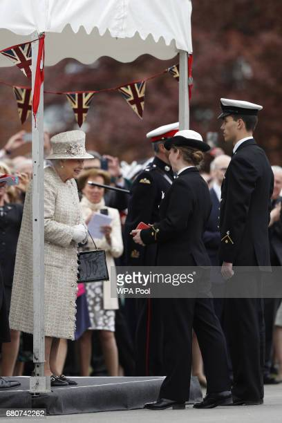 Britain's Queen Elizabeth II presents the Queen's gold medals to outstanding students and Chief Cadet Captains Ellen White and Fred Taucher during...