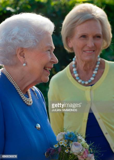 Britain's Queen Elizabeth II reacts as she greets British chef and television presenter Mary Berry as she visits the BBC Radio 2 Feel Good Gardens at...