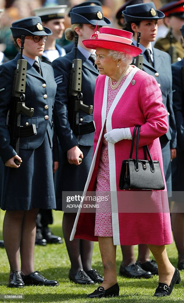 Britain's Queen Elizabeth II reacts as she inspects a Guard of Honour during her visit to Berkhamsted School, north-west of London on May 6, 2016, on the 475th Anniversary of its foundation. The Queen, in her role as Patron of the school, will inspect a Guard of Honour formed from the school's Combined Cadet Force, and view displays celebrating various aspects of school life. Berkhamsted School was founded in 1541 by John Incent, Dean of St Paul's, initially as a school of just 144 pupils. Berkhamsted Schools Group is currently responsible for the education of over 1,800 pupils. / AFP / ADRIAN