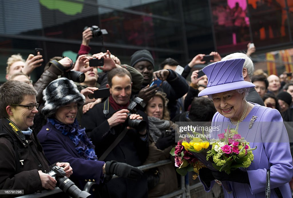 Britain's Queen Elizabeth II (R) reacts as she is given flowers following a visit to the new Royal London Hospital building and the new National Centre for Bowel Research and Surgical Innovation in London on February 27, 2013. The Queen accompanied by the Duke of Edinburgh toured the building, visiting the new Children's Services area meeting patients and staff. They also visited the new National Centre for Bowel Research and Surgical Innovation where they toured state-of-the-art laboratories dedicated to the study of human tissue. AFP PHOTO / POOL / ADRIAN DENNIS