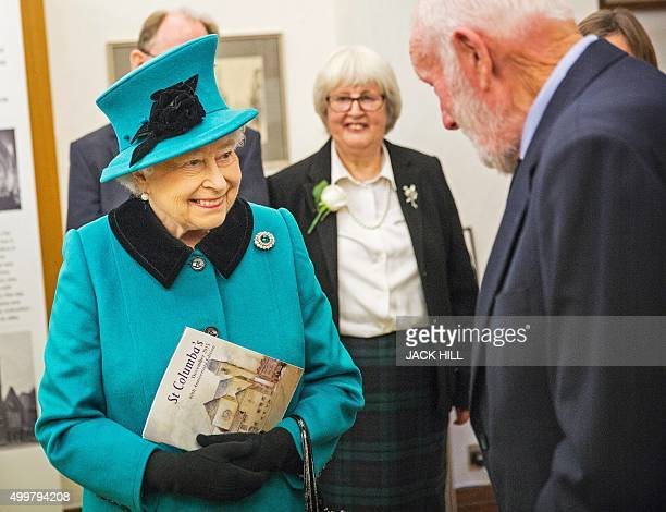 Britain's Queen Elizabeth II reacts as she meets Roger Claypit the stonemason who laid the foundation stonewith Queen Elizabeth The Queen Mother in...