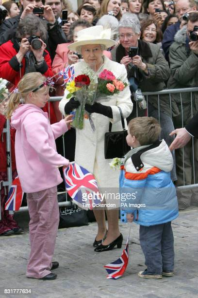 Britain's Queen Elizabeth II receives flowers during her walkabout in Guildford High Street after distributing Maundy Money at Guildford Cathedral