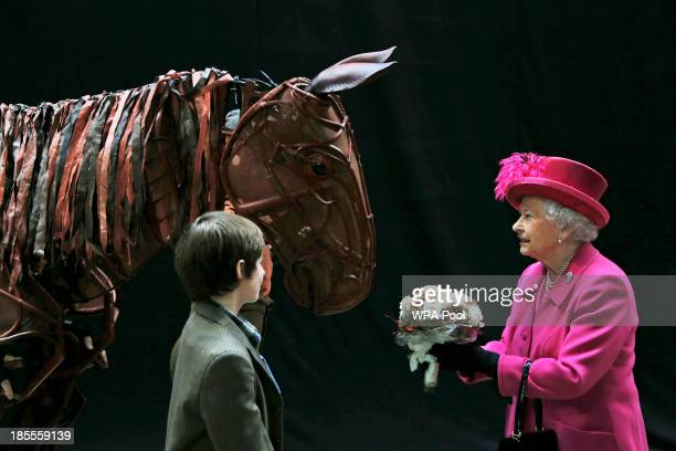 Britain's Queen Elizabeth II receives flowers from a child actor as she inspects the horse prop from the theatre production 'War Horse' during a...