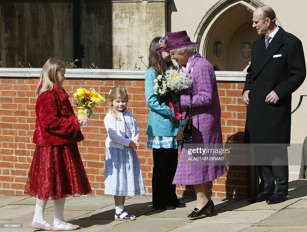 Britain's Queen Elizabeth II receives flowers from children as she leaves an Easter Sunday church service in Windsor on April 4, 2019.