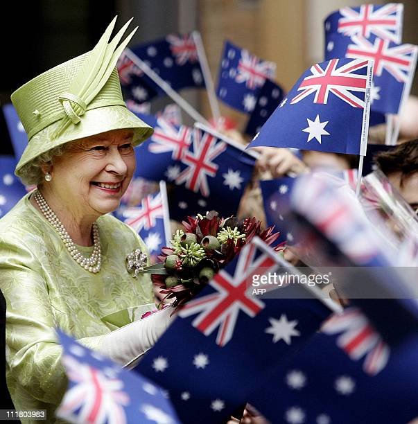 Britain's Queen Elizabeth II receives flowers from waiting school children waiving national flags after the Commonwealth Day Service in Sydney 13...