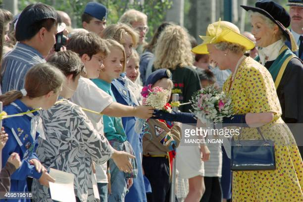Britain's Queen Elizabeth II receives flowers from wellwisherd on August 17 1994 accompanied by Chancellor of the University of Northern British...