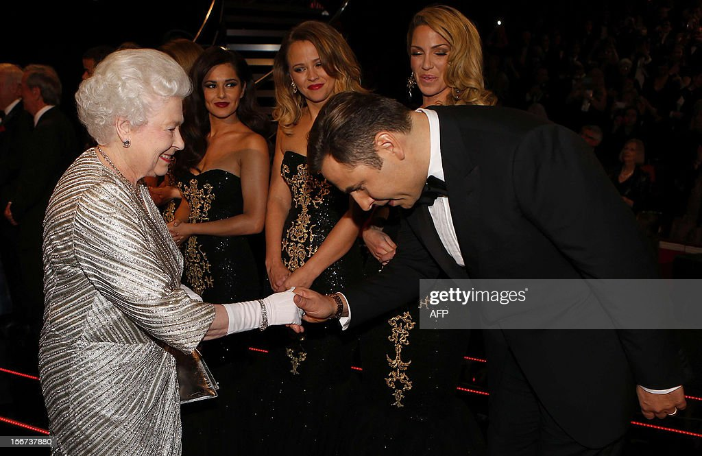 Britain's Queen Elizabeth II (L) shakes hands with British comedian David Walliams after the Royal Variety Performance at the Royal Albert Hall in London on November 19, 2012. The Queen, accompanied by The Duke of Edinburgh, attended the Royal Variety Performance in the show's 100th anniversary year where she met with stars of the show including Kylie Minogue, tenor Andrea Bocelli and the performing dog Pudsey.