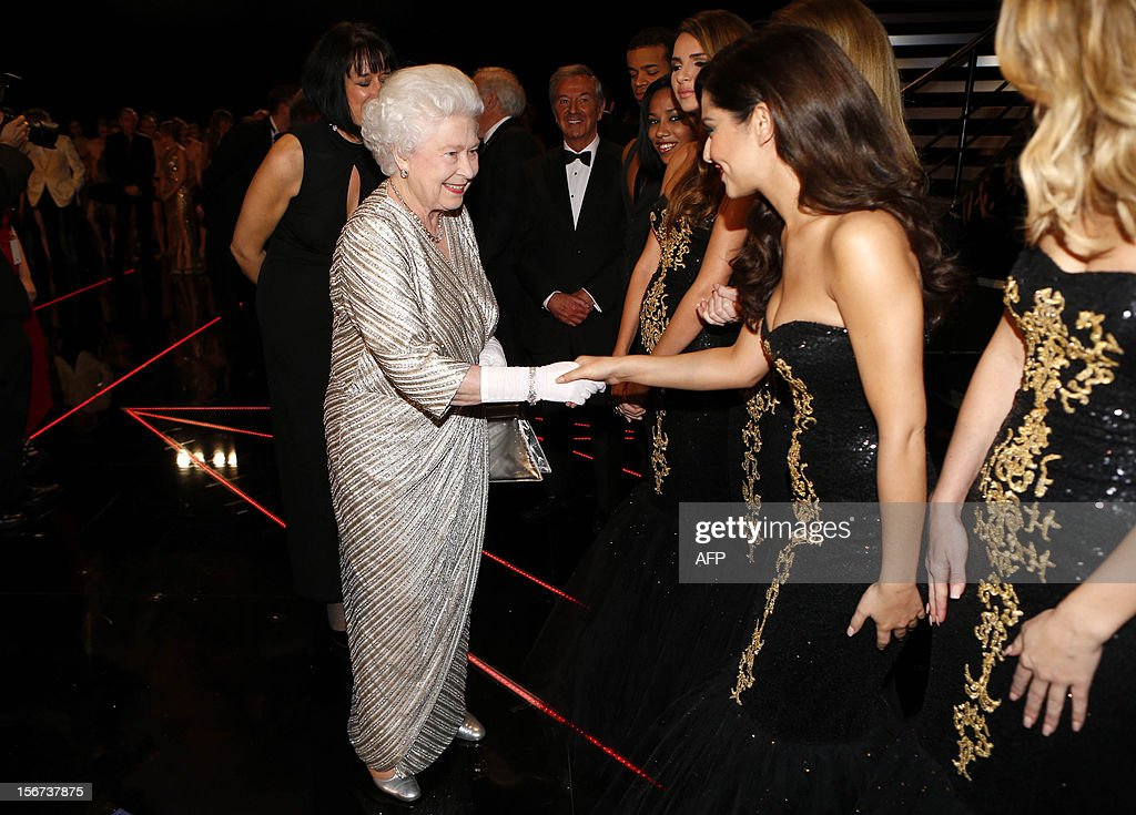 Britain's Queen Elizabeth II (L) shakes hands with Cheryl Cole from British-Irish pop band Girls Aloud after the Royal Variety Performance at the Royal Albert Hall in London on November 19, 2012. The Queen, accompanied by The Duke of Edinburgh, attended the Royal Variety Performance in the show's 100th anniversary year where she met with stars of the show including Kylie Minogue, tenor Andrea Bocelli and the performing dog Pudsey.