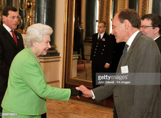 Britain's Queen Elizabeth II shakes hands with Sir Tim BernersLee the inventor of the World wide web before she relaunched the Monarchy website at...