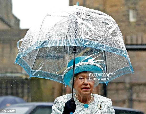 Britain's Queen Elizabeth II shelters from the rain beneath an umbrella as she arrives at Lancaster Castle in Lancaster northern England on May 29...
