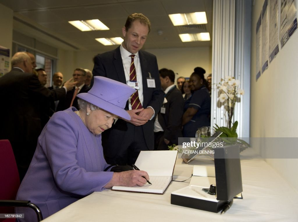 Britain's Queen Elizabeth II signs a commeorative book alongside Charles Knowles (back), Clinical Professor of Surgical Research, during a visit to the new National Centre for Bowel Research and Surgical Innovation in London on February 27, 2013. The Queen accompanied by the Duke of Edinburgh toured the new Royal London Hospital building, visiting the new Children's Services area meeting patients and staff. They also visited the new National Centre for Bowel Research and Surgical Innovation where they toured state-of-the-art laboratories dedicated to the study of human tissue.
