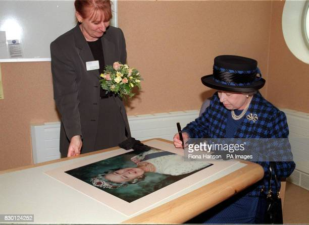 Britain's Queen Elizabeth II signs a large photograph of herself during her visit to officially open the new 35 million Day Surgery Centre at the...