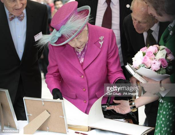 Britain's Queen Elizabeth II signs the visitor's book which she has signed twice previously in 1975 and 1936 during a visit to Coram children's...