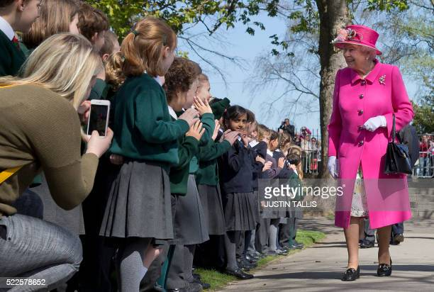 TOPSHOT Britain's Queen Elizabeth II smiles as she is greeted by school children as she arrives to open a bandstand at Alexandra Gardens in Windsor...