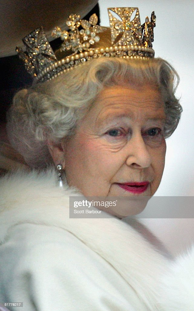 Britain's Queen Elizabeth II smiles as she looks out of the window of her horse drawn carriage as she leaves the Houses of Parliament after delivering her annual speech at the State Opening of Parliament on November 23, 2004 in London, England.