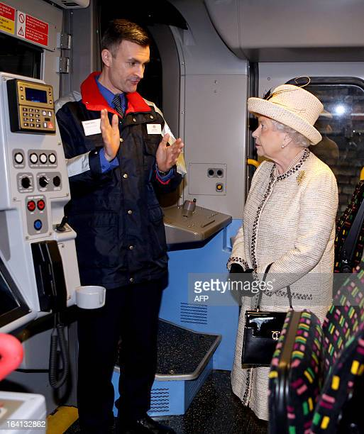 Britain's Queen Elizabeth II speaks with a Transport Of London employee as she tours a train during a visit to Baker Street tube station in central...