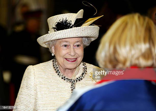 Britain's Queen Elizabeth II speaks with a Transport Of London employee during a visit to Baker Street tube station in central London on March 20...