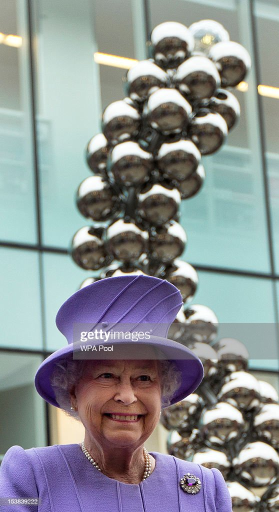 Britain's Queen Elizabeth II stands back-dropped by the Diamond Jubilee monument she unveiled to mark her 60 years on the throne on October 9, 2012 in Windsor, England. The sculpture was designed by Caroline Basra a 15-year-old pupil at Windsor Girl's School as her entry in a Windsor and Eton Society competition to find a worthy tribute to the Queen's Diamond Jubilee.