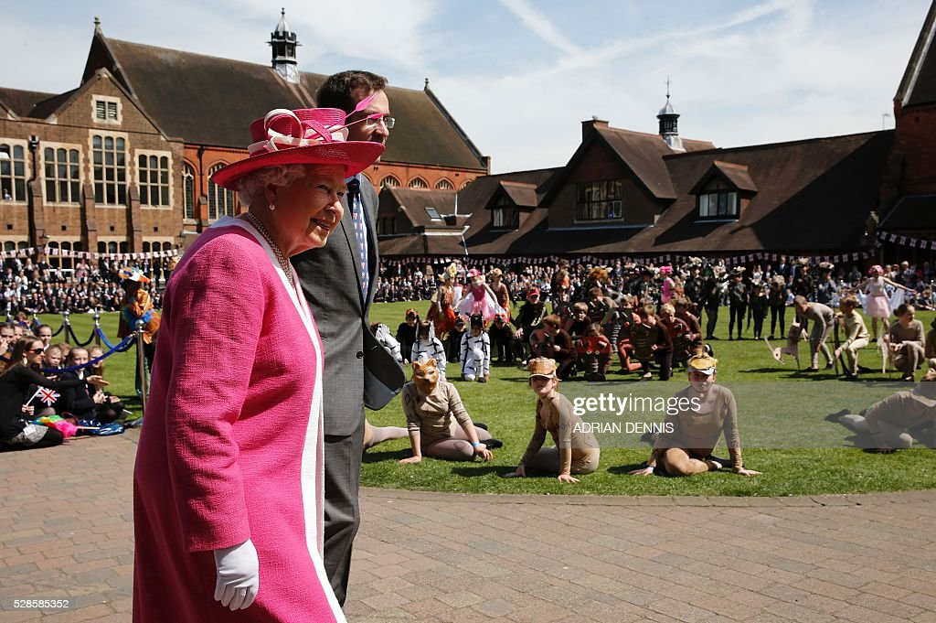 Britain's Queen Elizabeth II (R) stands with Berkhamsted School Principle, Richard Backhouse, as they watch a rendition of the the 'Lion King' during her visit to Berkhamsted School, north-west of London on May 6, 2016, on the 475th Anniversary of its foundation. The Queen, in her role as Patron of the school, will inspect a Guard of Honour formed from the school's Combined Cadet Force, and view displays celebrating various aspects of school life. Berkhamsted School was founded in 1541 by John Incent, Dean of St Paul's, initially as a school of just 144 pupils. Berkhamsted Schools Group is currently responsible for the education of over 1,800 pupils. / AFP / ADRIAN