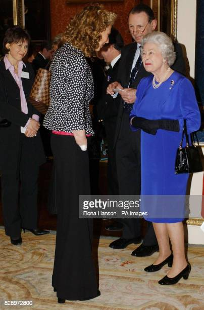 Britain's Queen Elizabeth II talks to Lawyer Olivia Giles who had her arms and legs amputated after contracting meningococcal septicaemia at a...