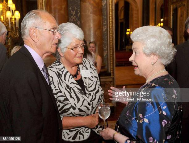 Britain's Queen Elizabeth II talks to Mr John Moddy and his wife Margaret of the Derry City Red Cross meals on wheels at a reception for the Queen's...