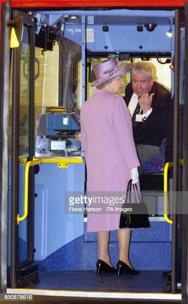 Britain's Queen Elizabeth II talks with bus driver Tony Farrell as she looks round a double decker bus in Willesden bus garage North London
