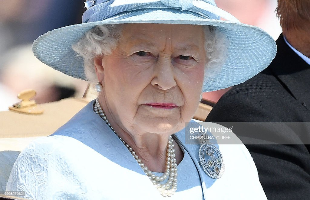 TOPSHOT - Britain's Queen Elizabeth II travels in a horse-drawn carriage past Buckingham Palace on her way to Horse Guards Parade for the Queen's Birthday Parade, 'Trooping the Colour', in London on June 17, 2017. The ceremony of Trooping the Colour is believed to have first been performed during the reign of King Charles II. In 1748, it was decided that the parade would be used to mark the official birthday of the Sovereign. More than 600 guardsmen and cavalry make up the parade, a celebration of the Sovereign's official birthday, although the Queen's actual birthday is on 21 April. / AFP PHOTO / Chris J Ratcliffe