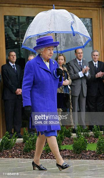 Britain's Queen Elizabeth II walks in the rain holding her umbrella during her visit to the new National Tennis Centre Roehampton in London 29 March...