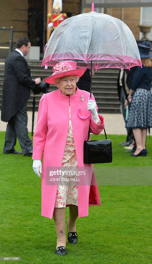 Britain's Queen Elizabeth II walks under an umbrella in the garden of Buckingham Palace in London as up to 8000 guests attend the first royal garden...