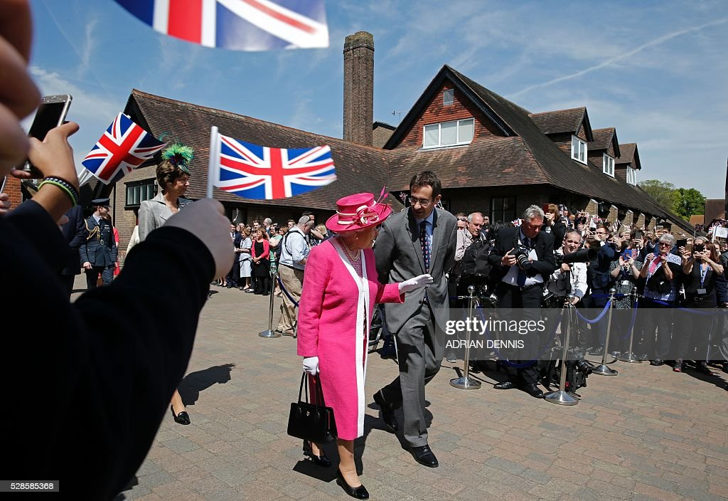 Britain's Queen Elizabeth II (C left) walks with Berkhamsted School Principle, Richard Backhouse, as she tours Berkhamsted School, north-west of London on May 6, 2016, on the 475th Anniversary of its foundation. The Queen, in her role as Patron of the school, will inspect a Guard of Honour formed from the school's Combined Cadet Force, and view displays celebrating various aspects of school life. Berkhamsted School was founded in 1541 by John Incent, Dean of St Paul's, initially as a school of just 144 pupils. Berkhamsted Schools Group is currently responsible for the education of over 1,800 pupils. / AFP / ADRIAN