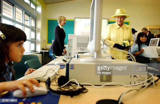 Britain's Queen Elizabeth II watches pupils using computers in the computer room at Keys Meadow Primary school a new primary school in Enfield Lock *...