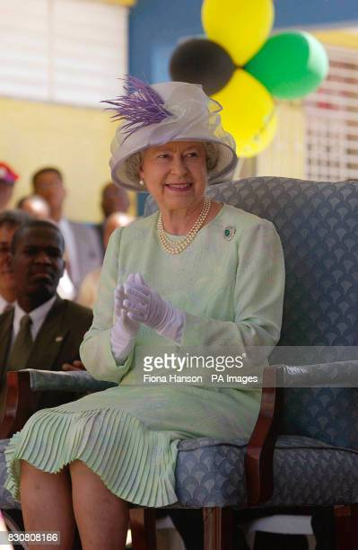 Britain's Queen Elizabeth II watches schoolchildren perform at a cultural entertainment at the Hugh Sherlock School Trenchtown Jamaica during her...