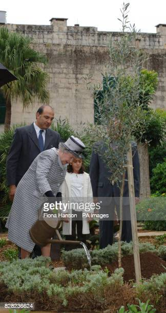 Britain's Queen Elizabeth II waters an olive tree she has ceremonially planted in the grounds of San Anton Palace Malta accompanied by nineyearold...