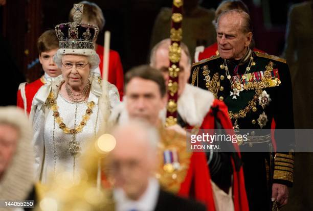 Britain's Queen Elizabeth II wearing the Imperial State Crown and Prince Philip Duke of Edinburgh proceed through the Royal Gallery in the Palace of...