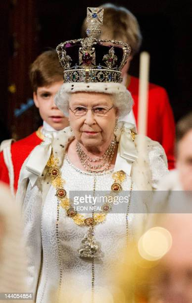 Britain's Queen Elizabeth II wearing the Imperial State Crown walks through the Royal Gallery in the Palace of Westminster home to the Houses of...