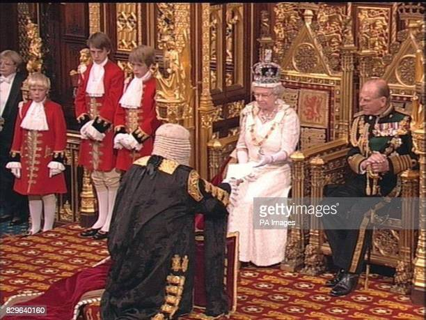 Britain's Queen Elizabeth II with the Duke of Edinburgh takes her speech from the Lord Chancellor in the House of Lords during the State Opening of...