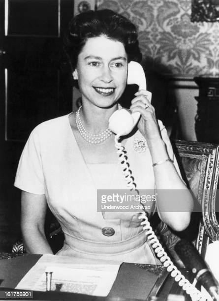 Britain's Queen Elizabeth talks to Canadian Prime Minister John Diefenbaker as she inaugurated the Canadian TransAtlantic Telephone cable system by...